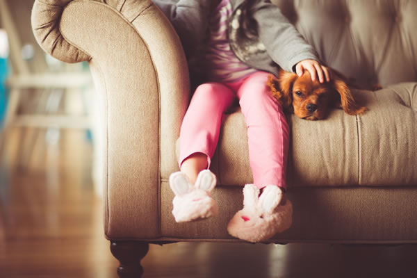 Picture of a child sitting on a couch with her dog